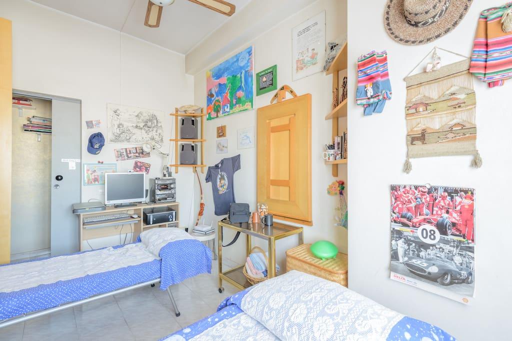 Sempre i due lettini della stanza visti dall'angolazione della finestra, il computer, e ninnoli e oggetti raccolti durante i viaggi nel mondo.