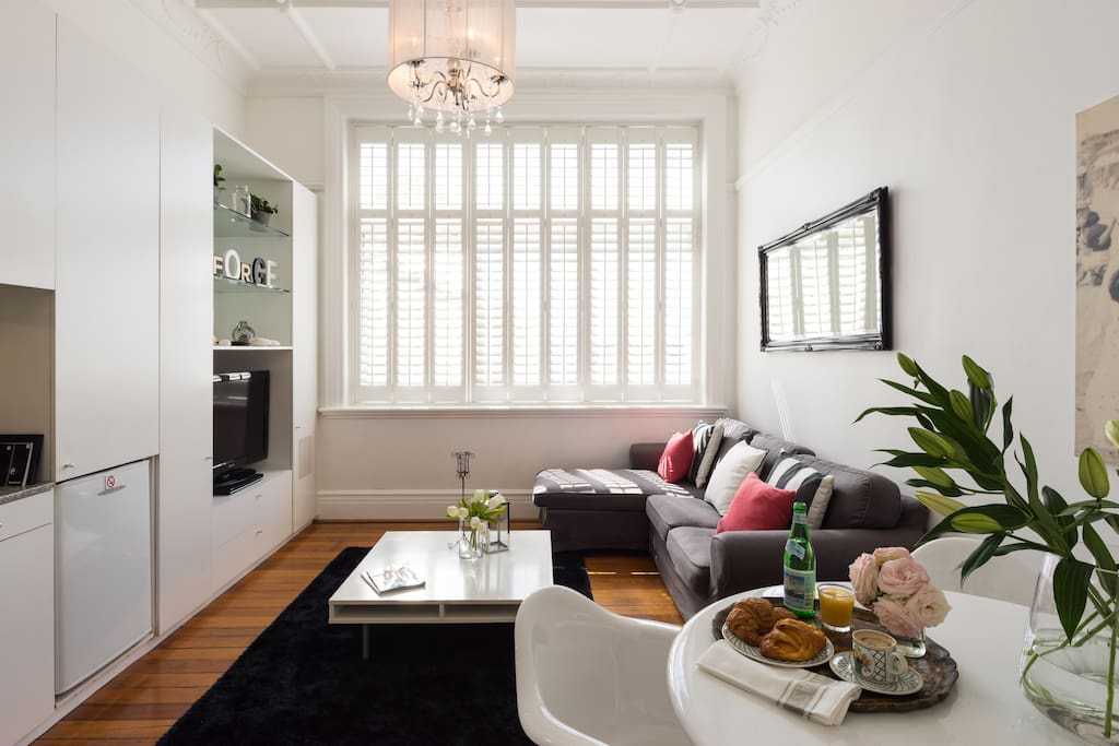 Sitting room with comfortable stylish furniture and late afternoon sun filtered through plantation shutters