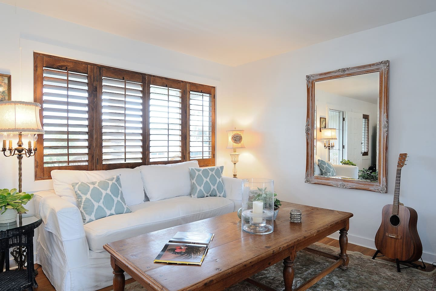 Living room features hardwood floors,  comfy down couch and plantation shutters.