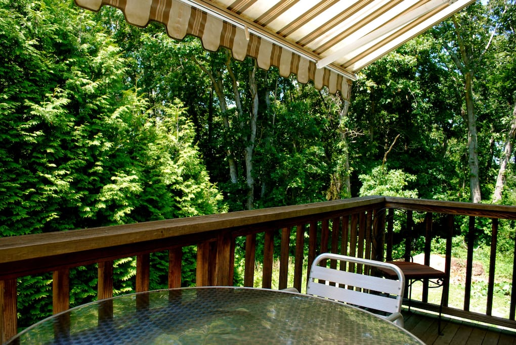 Private outdoor deck with retractable awning and woodland views.