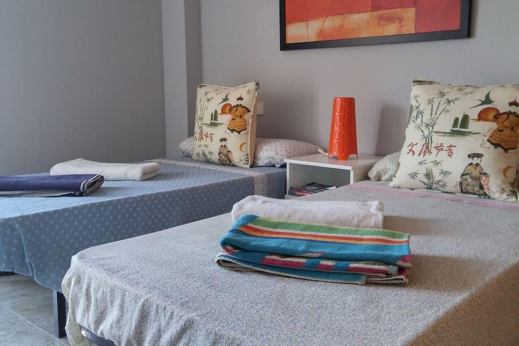 habitacion de huespedes con toallas de playa y de baño.