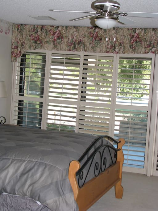 Master bedroom with plantation shutters and wall of glass overlooking pool.