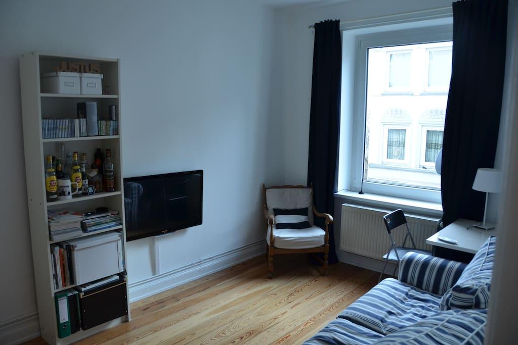 Wohnzimmer mit TV, Sofa ist ausklappbar und eine dritte Person kann darauf schlafen