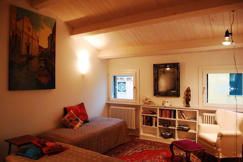 Persian carpets, Venetian mirror and lighting. Windows overlook the Riello.