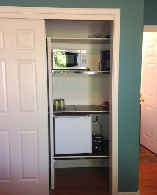 Pantry area with microwave, fridge, Kuerig coffee machine and toaster.