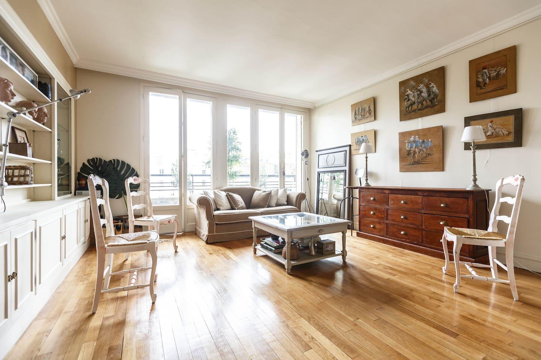 Grand salon ensoleillé sur des portes fenêtres donnant sur un balcon sans vis-à-vis