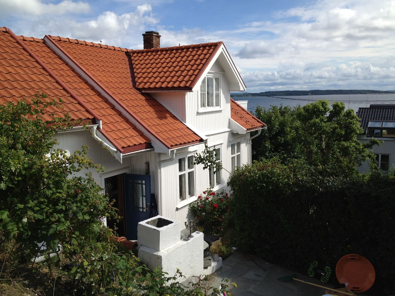 Wiew of the house from the upper level in the garden. The Oslo fjord in the background