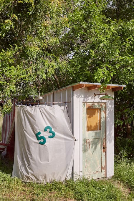 The separate yurt bathroom with full toilet, sink, and outdoor shower.