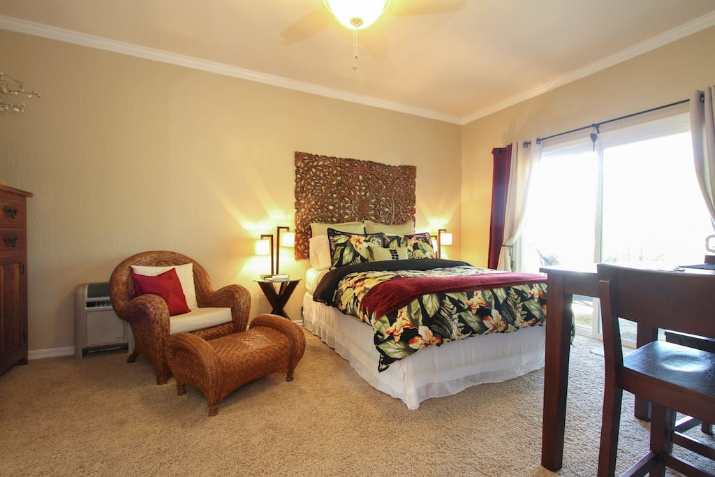 Relax in the comfort of a cozy queen bed with down comforter, Egyptian cotton sheets and lots of pillows. Enjoy your favorite book or watch TV in the rattan chair. Sliding door leads to private deck with sitting area, table and BBQ.