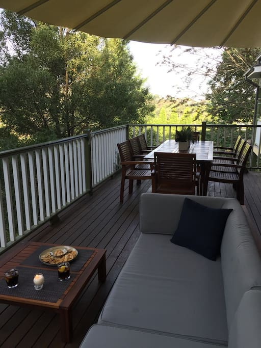 Dining and lounge area on large sunny deck overlooking the lush grounds and gardens