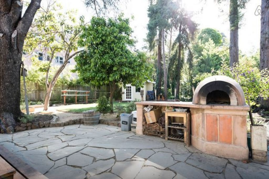 Large patio with cobb pizza oven and BBQ. Separate cottage/tinyhouse is visible in the background