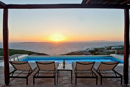 Cycladic Villa 270m2 with two outside, stone terraced areas both offering panoramic sea and sunset views with swimming pool, barbecue, sunbeds and comfortable seating areas for a luxurious and relaxing holiday in the sun on magical Mykonos.