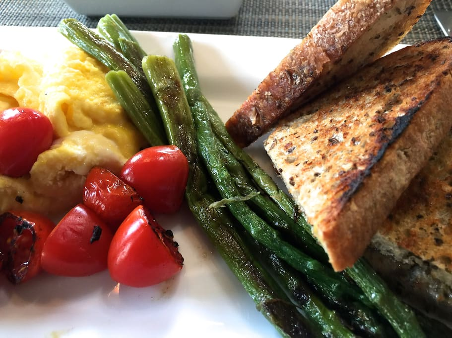 Fluffy scrambled egg and egg whites with cast iron grilled tomatoes and asparagus, with pumpkin seed toast