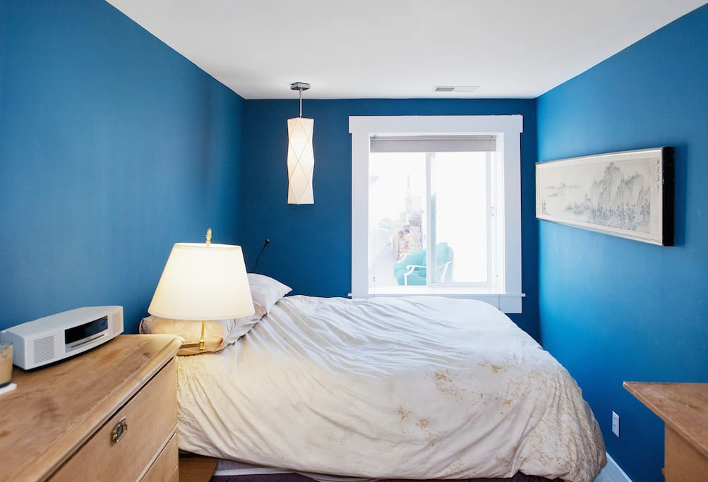 Sunny bedroom with comfy queen-sized bed, looking out on garden.