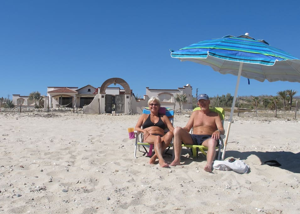 A couple of happy campers on the beach with the house behind.