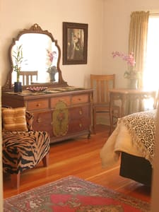 King bed with kitchenette and adjoining sitting room and full bath with a clawfoot soaking tub. Wood floors throughout light and bright with the large pictire window.  Tiger stripes and leopard accents make for this eclectic space an elegance all it's own.