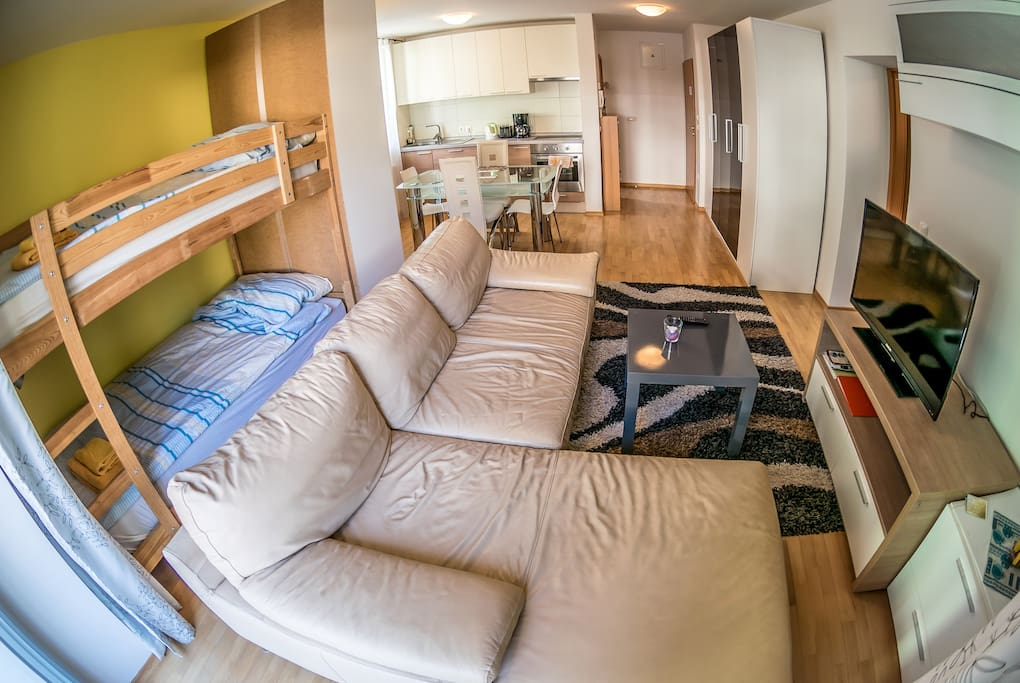 Living room area with bunk bed, couch, Tv and exit to private balcony