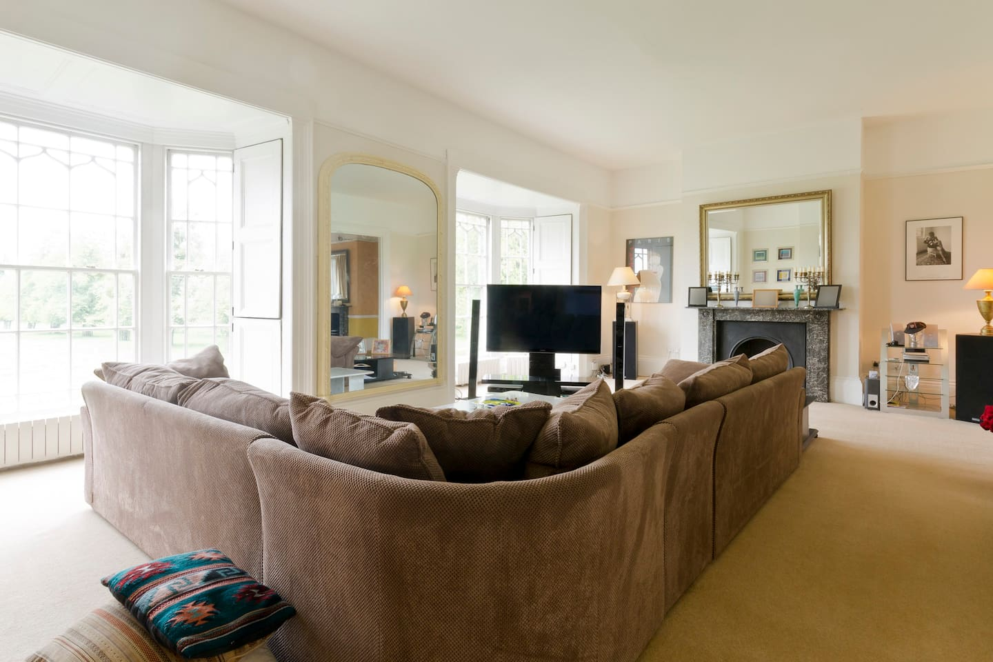 Large comfy lounge with two floor to ceiling windows overlooking Bushy  Park