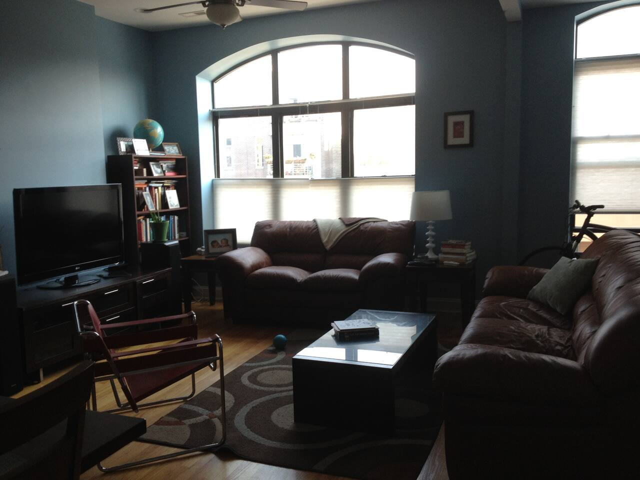 very sunny living room with comfy couch and love seat