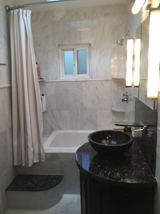 Skylit Marble Walls and Floor Modern Bathroom