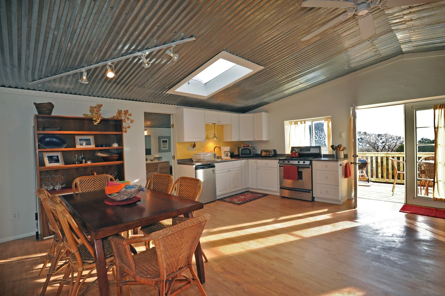 dining and kitchen areas with open doors to bathroom and main entrance from deck