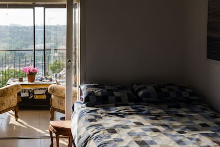 This amazing big room is a part of a penthouse. It has a nice balcony with a table and chairs that overlooks to a beautiful view of Jerusalem. It has a comfortable double bed, a big HDTV with cables, a quality sound system and a pouffe to chill out.
