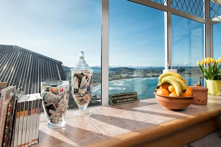 """Close to the city, overlooking the open sea. Double room & bed in sunny 3bedroom cottage, """"sitting in the sky"""". Opens to dramatic views of Lyall Bay, Evans Bay and the Tasman Sea. Having breakfast while watching penguins does happen. :)"""