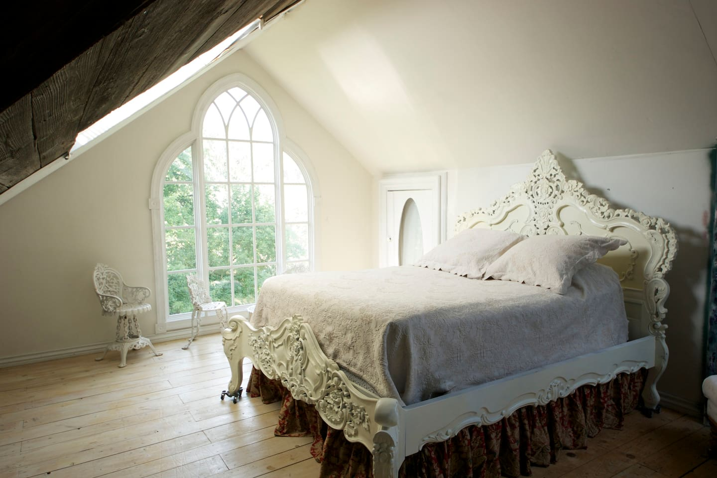 Attic Bedroom has queen bed, 3 chairs and footstools