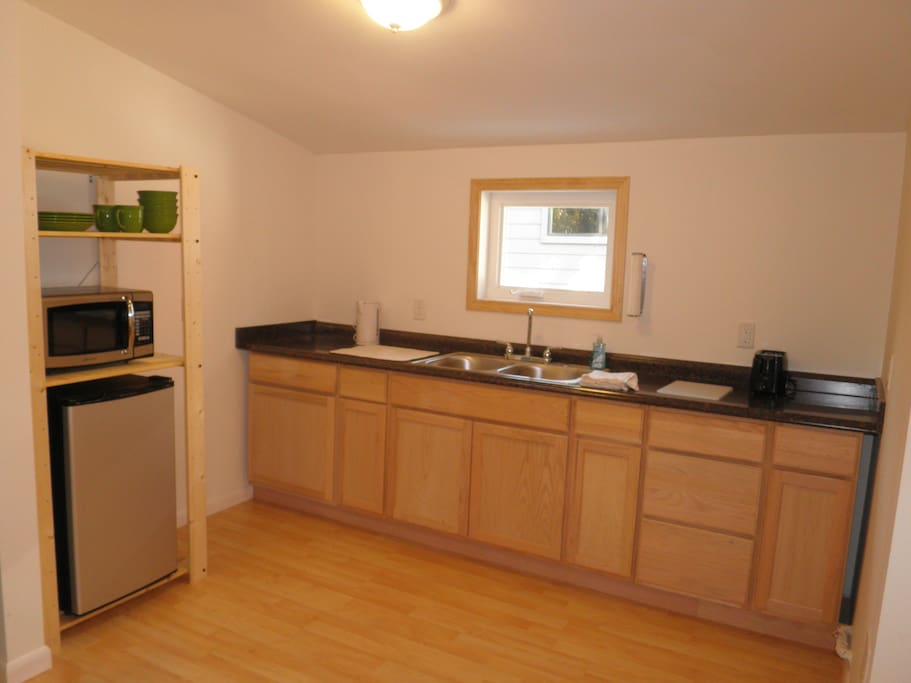 Kitchenette with mini fridge, microwave, electric kettle, toaster, dishes and silverware