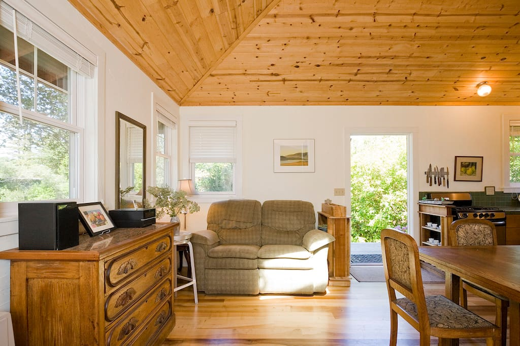 View from the bed into the living area.  Light floods into the space from windows, doors, and skylight.