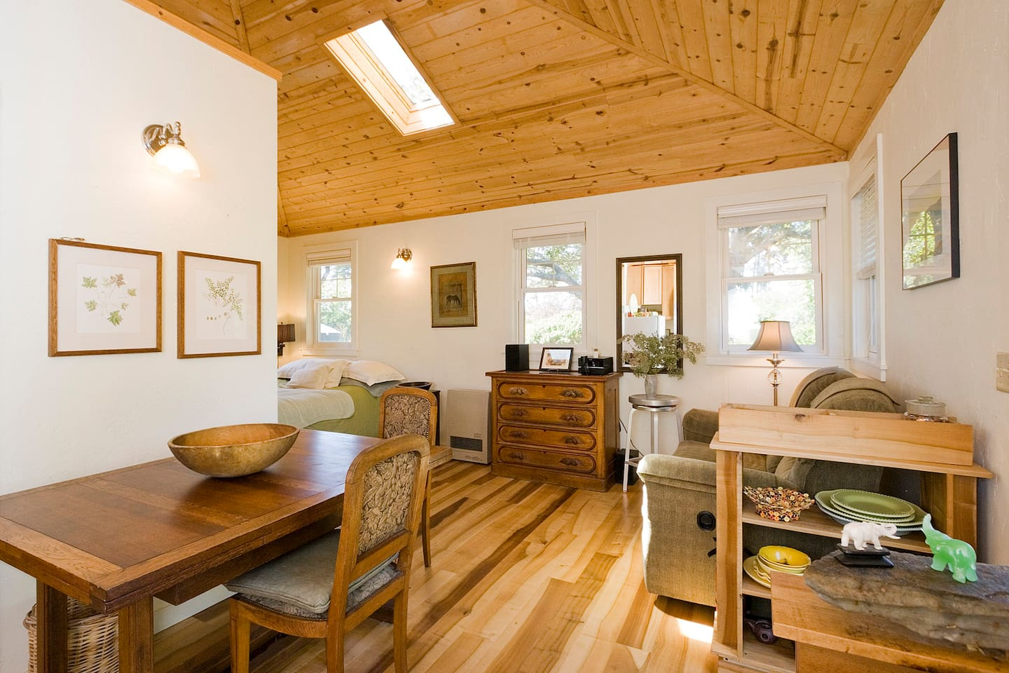 View of the dining table into the living area, showing the bay laurel floors.