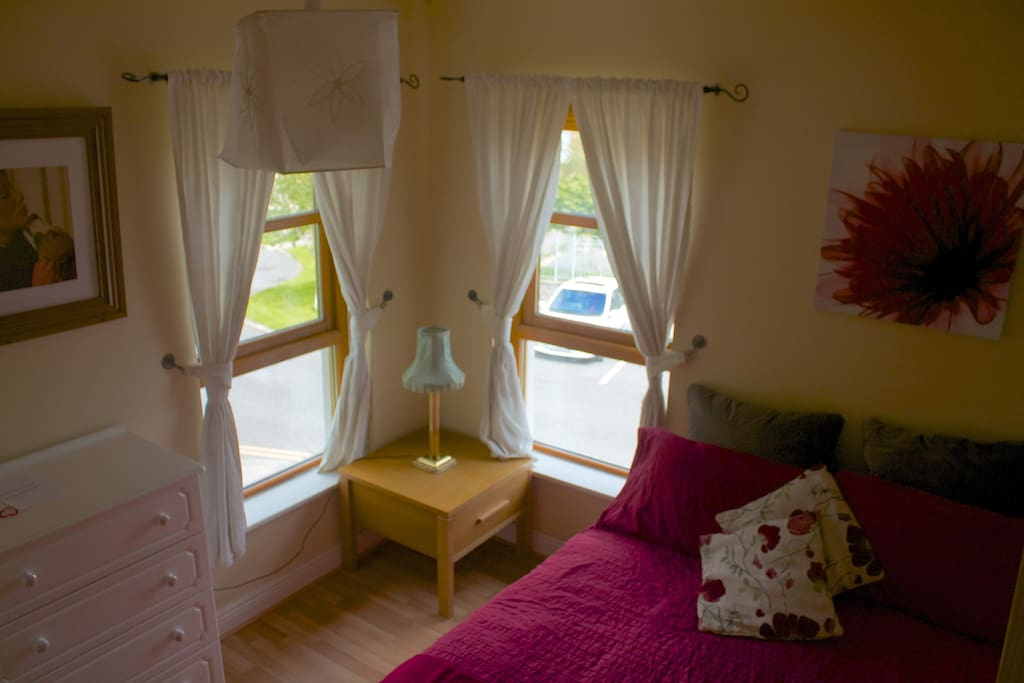 A cosy bedroom, well lit with plenty of storage space.