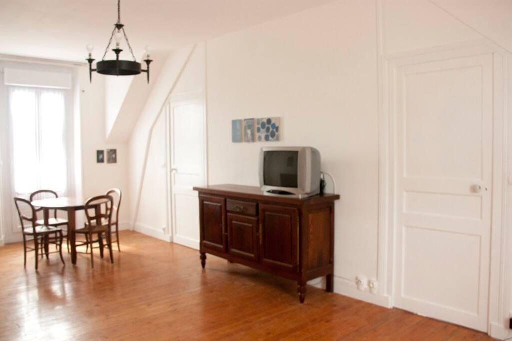 Salon-salle à manger avec table, buffet, canapé-lit et 2 fauteuils.