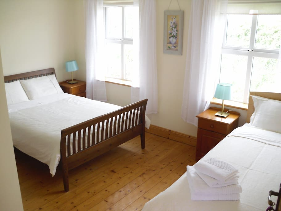 Triple room, with clean white linens.