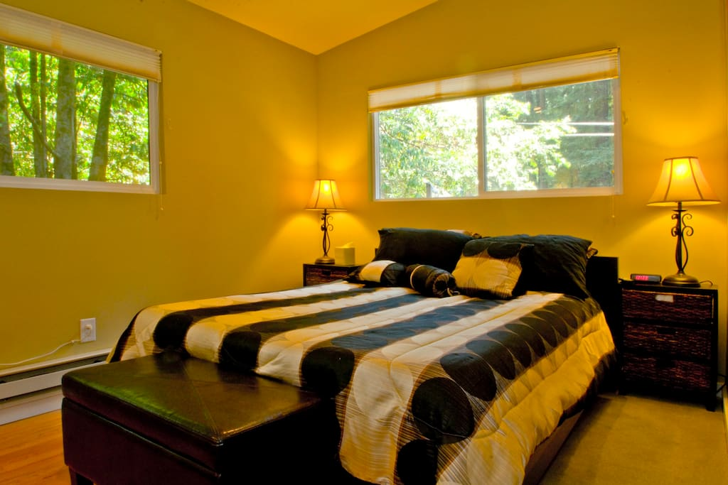 Bedroom #1 with Queen size bed with plush linens is bright and sunny windows with blinds