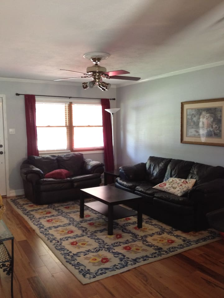 living room with leather couches and hardwood floors, central air and fans throughout
