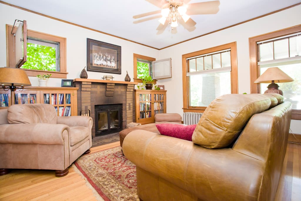 Living room with a wood burning fireplace, ample seating and lighting for reading and relaxing