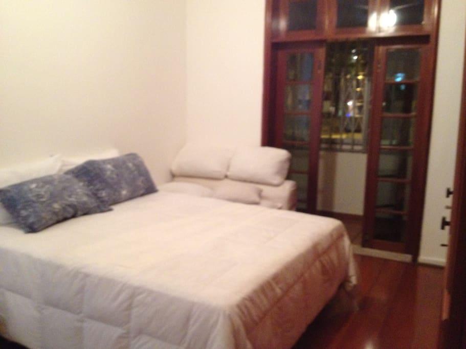 Suite com varanda, cama confortável e mais um sofá cama.