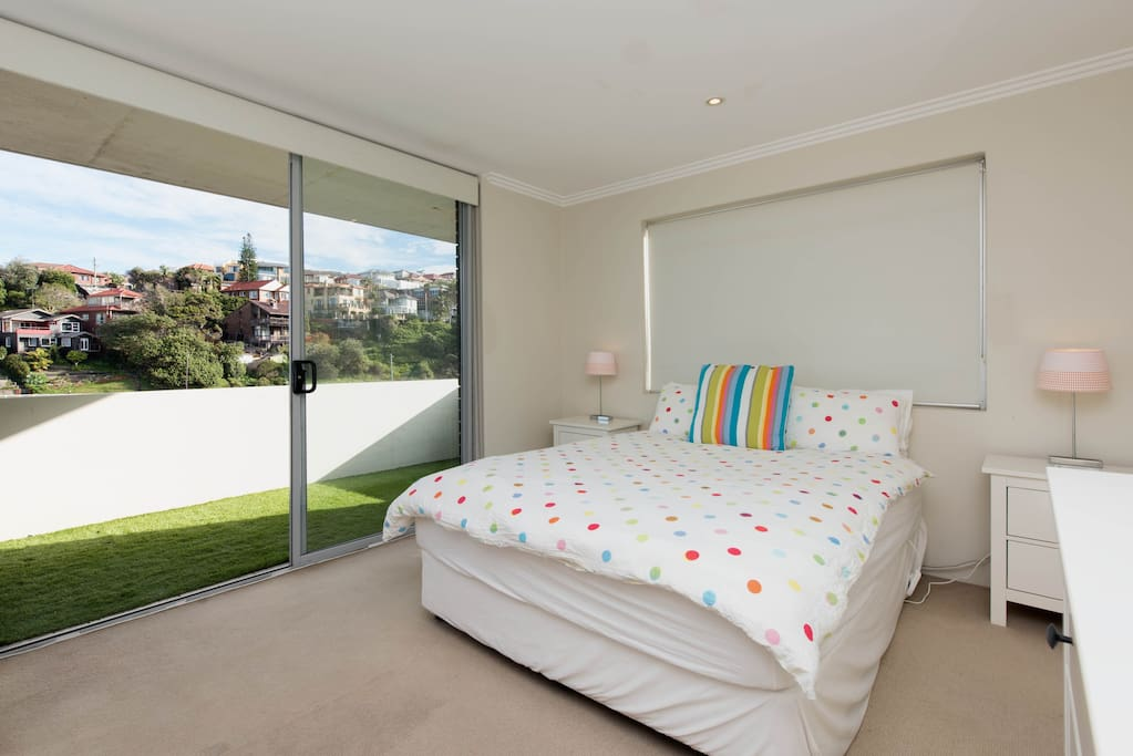 The Main Bedroom - sliding doors to the balcony and the lush (synthetic) grass. Have a sunny picnic outside on the lawn :)