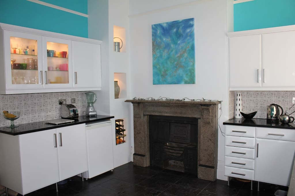 shared kitchen with marble fireplace and oil painting