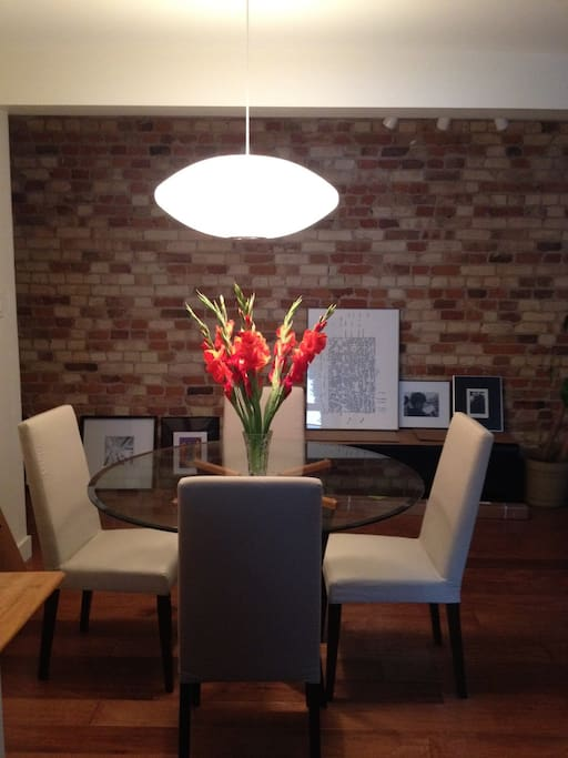 Night shot of dining room with exposed brick wall of art