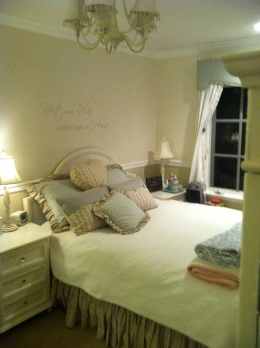 Queen bedroom with comfy bed and lots of lighting.