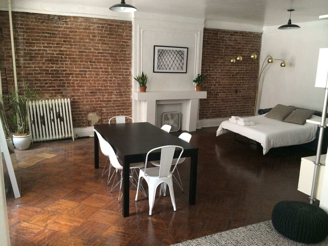 Exposed brick next to the sleeping area, table for planing trip around the city. mini fridge for keeping beverages cold (not pictured)