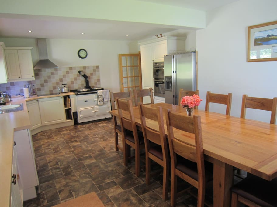 Large kitchen with oil fired aga, hob, double oven, american style fridge/freezer, table and chairs for 10
