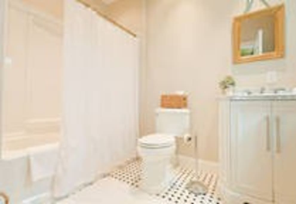 Attached Private Full Bath with tiled floors & white cabinetry with marbled top