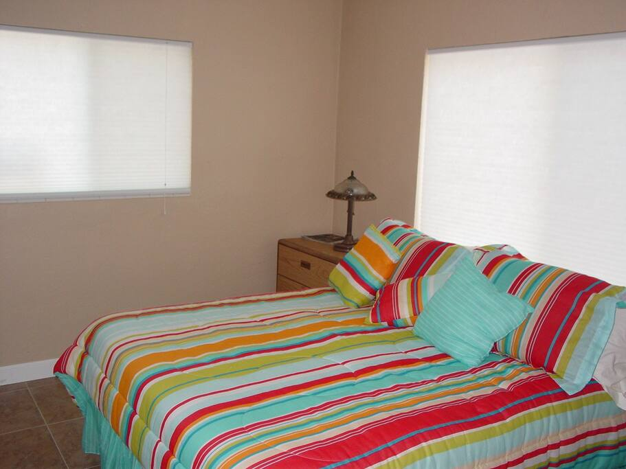 Bedroom with Queen bed and impact windows for security and noise reduction