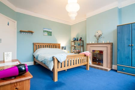 On the edge of Cheltenham, easy  to access as near bus and coach stops or off road parking. Large bedroom and run of the house. Big kitchen where we eat and comfy  living room with SKY TV.  Pretty garden and use of shed to secure bikes. Shy cat.