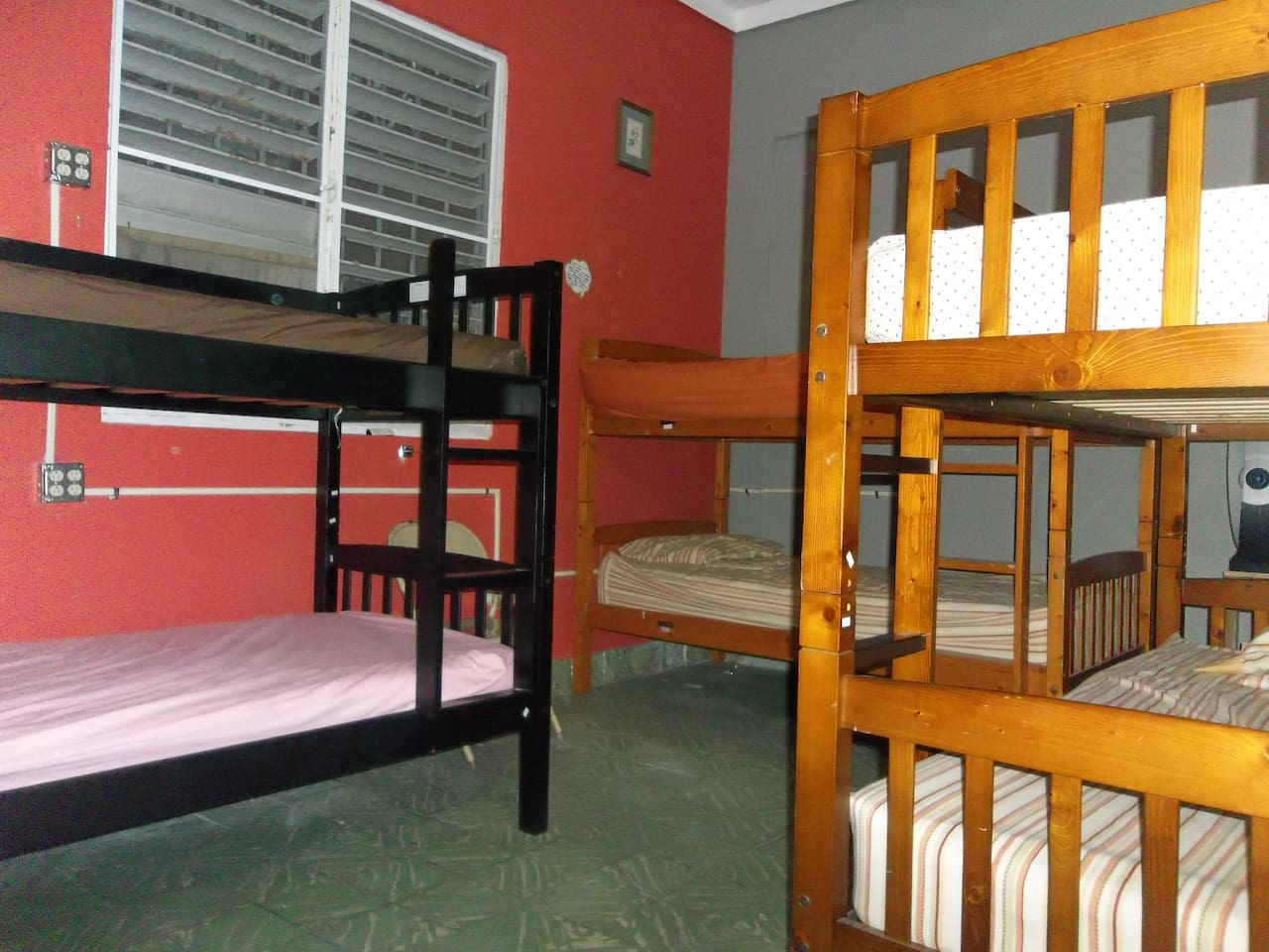 Three steady wooden bunk beds with electric outlets by each bed side