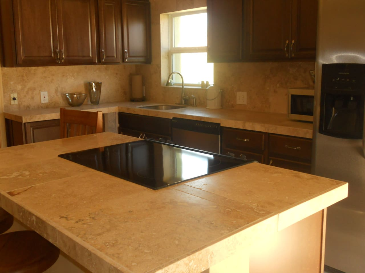 Recently remodeled kitchen with stainless steel, travertine counter tops, cook top and bar.