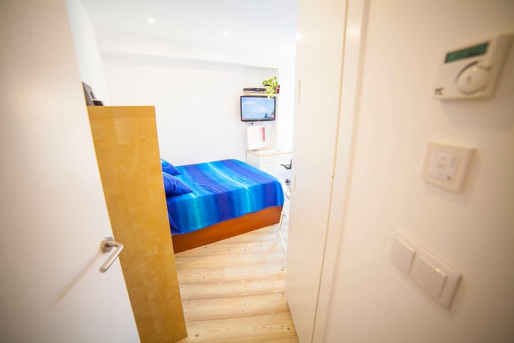 Room entrance , detailed individual thermostat and automation of blinds. Entrada a la habitación, detalle del termostato individual y de la domótica de las persianas
